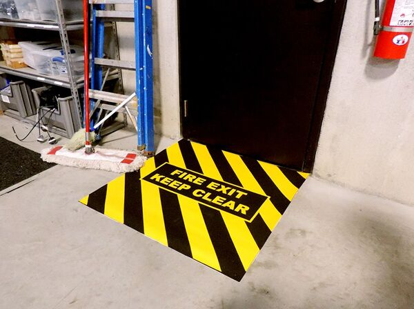 "Floormat Fire Exit Marker Floormat.com The Fire Exit Marker offers an excellent solution for creating a faster, more efficient clear zone for fire exits. <ul> <li>Come pre-printed with ""FIRE EXIT"" and ""KEEP CLEAR""</li> <li>One piece adhesive  backed  Hazzard Yellow and Black  chevrons coated with aluminum oxide grit </li> <li>Walking surface  comes complete with an industry standard anti-slip surface </li> </ul>"