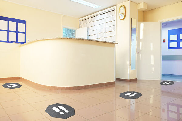 """Stick and Stand in place front desk 900x600 1 Floormat.com Stick-and-Stand mats are adhesive-backed social distancing mats designed to mark a safe place for customers to stand while waiting in lines.<strong>Sold by case only, with 6 mats per case.</strong> <ul> <li>Universal """"stop sign"""" shape with shoe prints marks where customers should stand; mats can be placed at safe intervals in virtually any configuration.</li> <li>Adhesive backing keeps the mat flat and in place, even with heavy cart and buggy traffic.</li> <li>Mats can be left in place during daily floor cleaning; floor scrubbers, mops, and brooms will pass right over them without causing damage.</li> <li>Less likely than floor decals to leave a sticky residue.</li> <li>Treated with an anti-microbial formula for protection from odors.</li> <li>Low-profile design with a high-traction surface to enhance slip resistance.</li> <li>Mat lifetime is up to 3 to 4 months under normal use.</li> </ul>"""