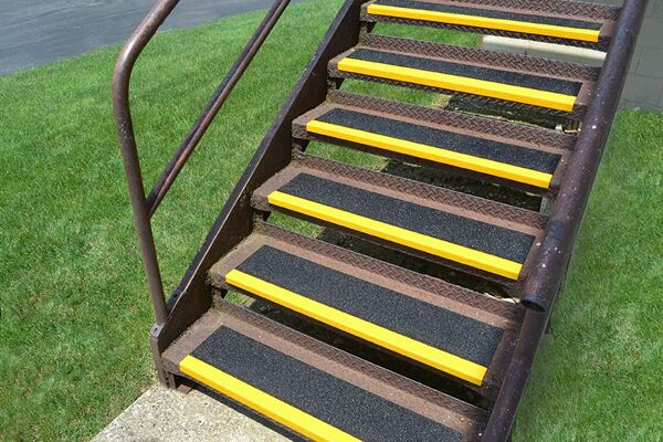 """Grit Coated Fiberglass Step Cover Floormat.com Grit-Coated Step Covers & Walkway Panels provide slip resistance, durability and a permanent anti-slip solution. Fiber glass step covers are lightweight and ideal for use on structurally sound surfaces. <ul> <li>Our Fiber Glass products are coated with a proprietary blend of mineral abrasive epoxy grit. Surfaces such as gratings, mezzanines, steps, inclines, and Ramps</li> <li>All are available in three distinct grit coating options: Heavy Duty, Medium and Fine as well as Yellow or Black.</li> <li>Specialty sizes and panels are available upon request. Call for details.</li> </ul> <h2>Add Slip-resistance to Steps, Ramps & Walkways</h2> Featuring a proprietary coating of mineral abrasive epoxy grit, our fiberglass step covers and walkways provide a lightweight and durable anti-slip surface. With three coating options, heavy, medium or fine, our covers may be applied to any structurally sound surface including steps, inclines, floors, and ramps. These fiberglass covers are a cost-effective way to provide slip-resistant footing to existing surfaces, and combine low maintenance with long service life.The mineral abrasive epoxy grit is bonded to 0.125"""" thick thermoset polyester, fiber-reinforced polymer panels. These fiberglass step covers and panels are fire-retardant and easy to maintain. The epoxy grit surface may be swept to loosen and remove dirt, and cleaned with a general purpose industrial floor cleaner and bristle brush. The step covers and walkway panels may also be pressure washed with up to 1000 psi.<img class=""""size-medium wp-image-14990 alignleft"""" src=""""https://www.floormat.com/wp-content/uploads/sure-foot-grit-300x232.jpg"""" alt="""""""" width=""""300"""" height=""""232"""" /> <h3>Step Covers</h3> <ul> <li>11.75"""" depth with 2"""" nosing</li> <li>9"""" depth with 1"""" nosing</li> <li>3"""" depth with 1"""" nosing</li> <li>Lengths up to 12 feet</li> <li>Single color treads in yellow or black only</li> <li>Two-color treads, yellow nose with black ba"""