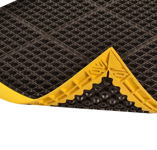 Safety Stance 2 Floormat.com Safety Stance® is made from a grease resistant rubber compound to withstand many of the more commonly found industrial cutting oils and chemicals. Particularly well suited for wet or dry work areas, Safety Stance® features a large hole drainage system with a mini-diamond studded top surface to minimize slippage. Beveled edges are made from a 100% Nitrile rubber compound offering the same resistance to oils/chemicals as the mat. <ul> <li>100% Nitrile rubber compound withstands many common industrial cutting fluids, oils and chemicals</li> <li>Large hole configuration facilitates drainage and resists clogging</li> <li>Raised studs on top surface add traction</li> <li>Colored beveled borders are permanently affixed to the mat and are available on 3 or 4 sides</li> </ul>