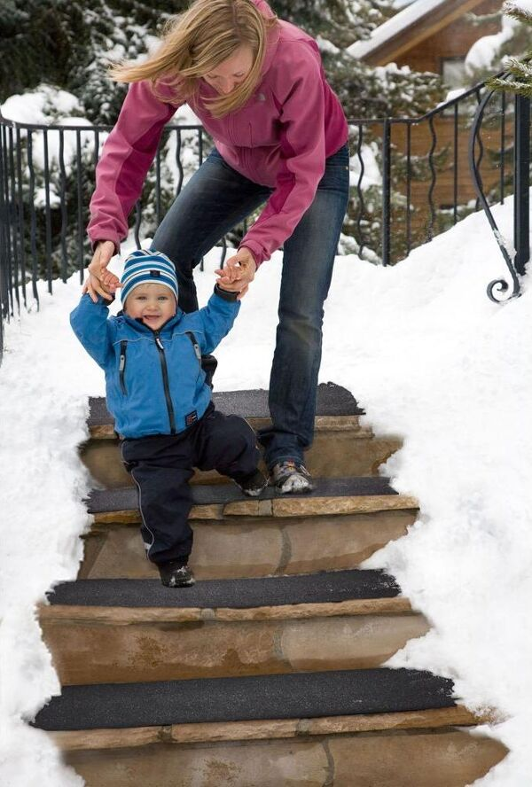 """Woman Baby heated steps Floormat.com Outdoor heated mats and heated stair treads melt snow & ice for safe footing without shoveling or chemicals. <b>(GFCI Power Cord not included.)</b> <ul> <li>GFCI Power Unit can connect up to 10 stair tread mats or 5 doormats or 4 walkway mats or any combination thereof, up to 15 amps.</li> <li>GFCI Power Unit Not Included</li> </ul> <h2>Residential Snow Melting Mats and Stair Treads for Safer Homes</h2> <strong>These heated mats prevent snow and ice accumulation on walkways and stairs around your home</strong>. Made of customized thermoplastic materials, the mats are portable and can be left outside for the entire winter season. Our heated mats will generate heat to melt snow at a rate of 2"""" per hour leaving your pathway to the home clean and clear 24/7. <strong>The Residential Heated Walkway Mat and Heated Stair Mat</strong> can be used independently or interconnected with one another to create a continuous system of snow melting mats. With the mats' built in watertight connector cables, you can Mix and Match walkway and stair mats to create your perfect snow melting solution - all on a single plug!<b>Heated Walkway Mats & Heated Stair Tread Mats</b> Payments are processed on a secure server. <h3>Customer Testimonials</h3> <div>""""We love our heated stair mats. They are working great during this cold Michigan winter."""" - Craig, Lansing, MI""""This is the best purchase I have made on a New product in ages! It performs better than I could believe! The safety advantage is outstanding. We get a lot of snow and this product kept up with Mother Nature wonderfully. I would give it 5 stars out of 5!"""" - Lexy, Alpine, NJ""""Purchased two about a month ago for my uncovered porch and deck. First tested by putting on deck with several inches of snow; the area was DRY in the morning! Have kept mat on front porch and it has handled more than the 2 inches of snow per hour stated! And we have had plenty--16 inches in one week!"""" - Gwen, Batavia, IL""""I live"""