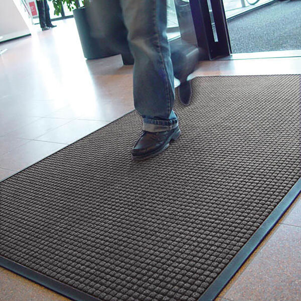 """guzzler 4 Floormat.com Guzzler™ is intended for use in medium to heavy traffic areas, the raised, crushproof waffle design of Guzzler™ aggressively scrapes and cleans, while the rubber-edged perimeter entraps dirt and moisture for superior water and soil control. Molded rubber """"cleats"""" on the underside of the mat grip the underlying surface minimizing mat movement. <ul> <li>High/low waffle pattern facilitates scraping and keeps moisture and debris away from foot traffic</li> <li>Raised rubber border on all 4 sides traps moisture and debris for easy removal</li> <li>Molded rubber cleats on the bottom of the mat grip underlying surfaces and minimize mat movement</li> <li>26 ounces of tufted yarn per square yard</li> <li>3/8 inch overall thickness for use in narrow clearance doorways</li> </ul>"""