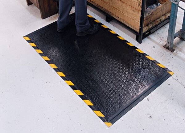 """happy feet textured 2 Floormat.com Happy Feet is a heavy-duty anti-fatigue mat that features a dense foam cushion encapsulated in nitrile rubber, making it suitable for both wet and dry environments. <ul> <li><b>Comfortable</b>- 1/2"""" dense foam cushion and nitrile rubber surface provide excellent anti-fatigue qualities</li> <li><b>Safe</b>- Certified high-traction by the National Floor Safety Institute (NFSI)</li> <li><b>Durable</b>- Nitrile rubber surface is penetration proof; borders will not crack or curl</li> <li><b>Versatile</b>- Welding safe; grease/oil proof; chemical resistant; ESD rating of electrically conductive</li> <li>Available in two surface types:<i>Textured Surface</i>for dry/damp environments or<strong><a href=""""https://www.floormat.com/floor-mats/anti-fatigue-mats/happy-feet-grip/""""><i>Grip Surface</i></a></strong>for wet environments where additional traction is needed</li> <li>Available with solid black or with OSHA-approved yellow striped borders</li> </ul>"""